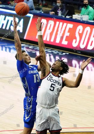 Stock Photo of Creighton forward Christian Bishop (13) shoots against Connecticut forward Isaiah Whaley (5) in the second half of an NCAA college basketball game in Storrs, Conn