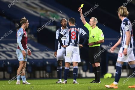 Referee Martin Atkinson shows a yellow card to Aston Villa's Jack Grealish, left, during the English Premier League soccer match between West Bromwich Albion and Aston Villa at the Hawthorns, West Bromwich, England