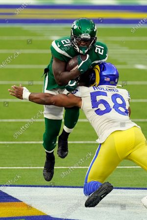 New York Jets running back Frank Gore, top, is tackled by Los Angeles Rams linebacker Justin Hollins (58) during the second half of an NFL football game, in Inglewood, Calif