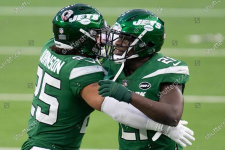 New York Jets running back Ty Johnson (25), left, celebrates the team's win over the Los Angeles Rams with running back Frank Gore (21) during an NFL football game, in Inglewood, Calif