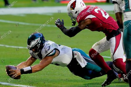 Philadelphia Eagles quarterback Jalen Hurts (2) dives for a touchdown as Arizona Cardinals cornerback Patrick Peterson (21) defends during the second half of an NFL football game, in Glendale, Ariz