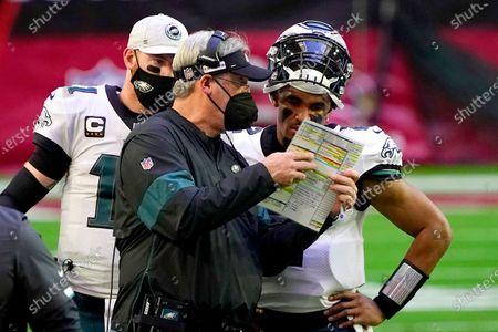 Philadelphia Eagles head coach Doug Pederson talks with starting quarterback Jalen Hurts as quarterback Carson Wentz (11) looks on during the first half of an NFL football game, in Glendale, Ariz