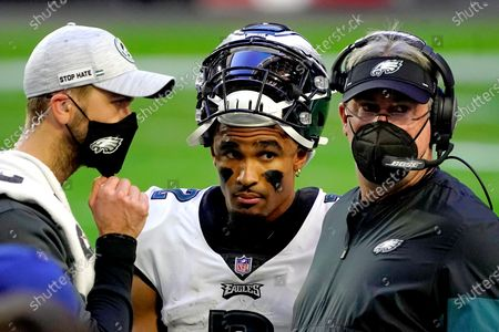 Philadelphia Eagles quarterback Jalen Hurts, center, talks with head coach Doug Pederson during the second half of an NFL football game against the Arizona Cardinals, in Glendale, Ariz