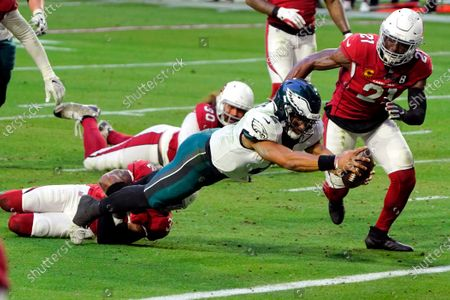 Philadelphia Eagles quarterback Jalen Hurts (2) dives in to the end zone for a touchdown as Arizona Cardinals strong safety Budda Baker and cornerback Patrick Peterson (21) defend during the second half of an NFL football game, in Glendale, Ariz
