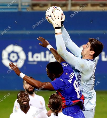 Eibar's midfielder Pape Diop (C) vies for the ball with Real Madrid's goalkeeper Thibaut Courtois (R) during the Spanish LaLiga soccer march between SD Eibar and Real Madrid held at Ipurua Stadium in Eibar, Spain, 20 December 2020.