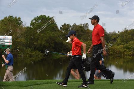 Stock Image of Tiger Woods and his son Charlie walk to the fairway after playing their tee shots on the second hole during the final round