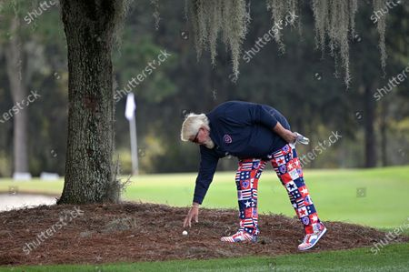 John Daly retrieves his ball under a tree along the first fairway during the final round of the PNC Championship golf tournament, in Orlando, Fla