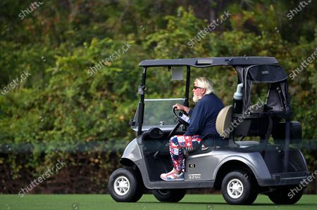 John Daly drives a cart on the first fairway during the final round of the PNC Championship golf tournament, in Orlando, Fla