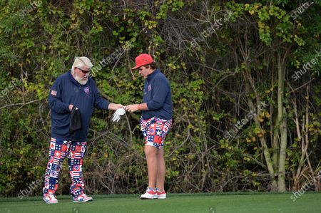 John Daly, left, hands a ball to his son, Little John Daly on the first fairway during the final round of the PNC Championship golf tournament, in Orlando, Fla