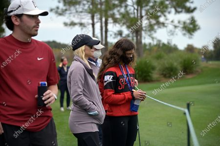 Elin Nordegren, center, and Sam Alexis Woods, right, watch Tiger Woods and Charlie Woods on the 10th green during the final round of the PNC Championship golf tournament, in Orlando, Fla