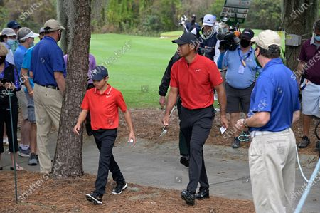 Tiger Woods and his son Charlie walk to the 11th tee during the final round of the PNC Championship golf tournament, in Orlando, Fla