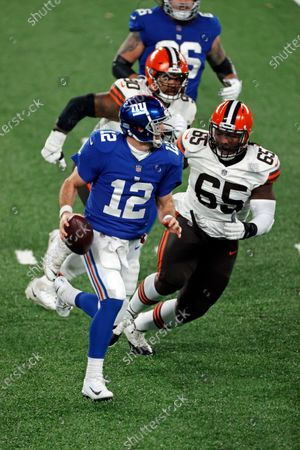 New York Giants quarterback Colt McCoy (12) scrambles away from Cleveland Browns defensive tackle Larry Ogunjobi (65) during an NFL football game, in East Rutherford, N.J