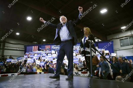 Stock Photo of Democratic presidential candidate Sen. Bernie Sanders, I-Vt., accompanied by his wife Jane O'Meara Sanders, right, arrives to speak during a primary night election rally in Essex Junction, Vt