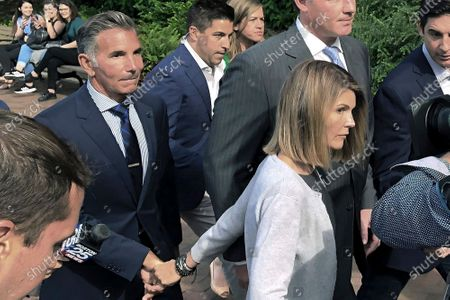 Stock Picture of Lori Loughlin and her husband Mossimo Giannulli, left, depart federal court in Boston. Loughlin reported to prison in October 2020, and Giannulli reported to prison in November 2020, after they pleaded guilty to charges in a nationwide college admissions bribery scandal