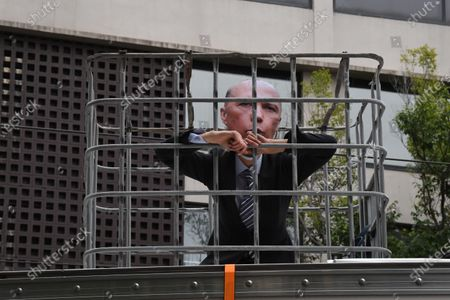 A prtest stands in a cage, wearing a mask dipicting Australian Minister for Home Affairs Peter Dutton, outside the location where refugees are being held in Melbourne, Australia, 21 December 2020. According to media reports, approximately 60 detainees have been transferred from a hotel in Melbourne's north to a former quarantine hotel in the city's inner suburbs.