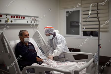 Stock Image of Nurse Mevlude Altan tends to Ismail Demir infected with COVID-19, at the intensive care unit of the Prof. Dr. Feriha Oz Emergency Hospital, in Istanbul, . The hospital is a new infirmary offering some of the most advanced intensive care treatment in the country. When the pandemic first struck, Turkey was credited for quickly bringing infection rates under control. It is now seeing an explosion in COVID-19 cases that is putting a serious strain on its health system
