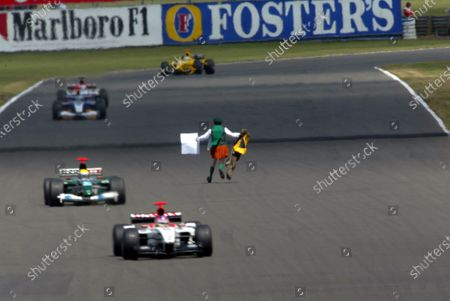 A kilt wearing lunatic aka Father Neil Horan (IRE) runs at the cars on the Hangar Straight during the race. Formula One World Championship, Rd11, British Grand Prix, Race Day, Silverstone, England, 20 July 2003. DIGITAL IMAGE