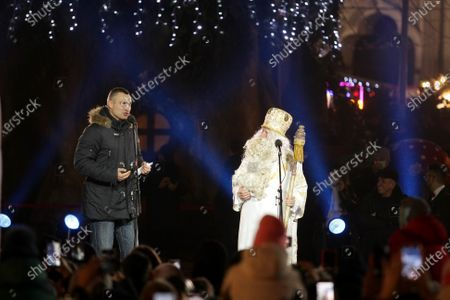 Stock Picture of Kyiv city head, Kyiv City State Administration head Vitali Klitschko (L) and an actor representing Saint Nicholas are seen on stage during the lighting of the country's main Christmas tree in Sofiiska Square on Saint Nicholas Day, Kyiv, capital of Ukraine.