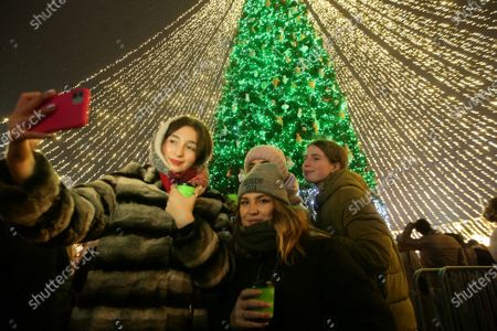 Girls pose for a selfie near the country's main Christmas tree during the lighting ceremony in Sofiiska Square that traditionally takes place on Saint Nicholas Day, Kyiv, capital of Ukraine.