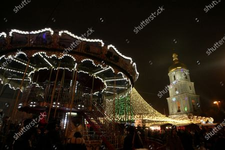 Stock Photo of A merry-go-round is situated the country's main Christmas tree in Sofiiska Square on Saint Nicholas Day, Kyiv, capital of Ukraine.