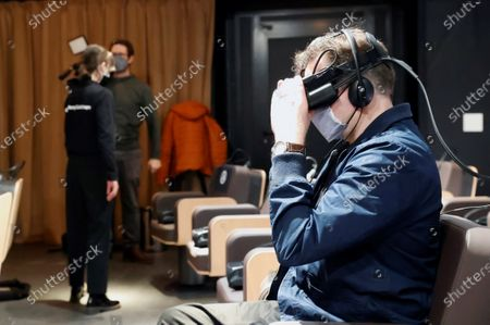 A visitor puts on a VR headset during the launching of Venezuelan orchestra director Gustavo Dudamel's project 'Symphony' at Madrid Royal Opera House, in Madrid, Spain, 21 December 2020. The touring virtual reality project featuring Gustavo Dudamel and 101 musicians from 22 countries is an experience to take classic music closer to all audiences allowing the spectator to be one other musician inside the orchestra.