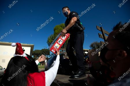 LAPD Officer Steve Rodriguez passes out toys on Saturday, Dec. 19, 2020 in Los Angeles, CA. Officers with LAPD's Newton Division joined Santa Claus as they towed his sleigh to visit the children of Pueblo Del Rio Housing Development and distributed Christmas toys. (Francine Orr / Los Angeles Times)