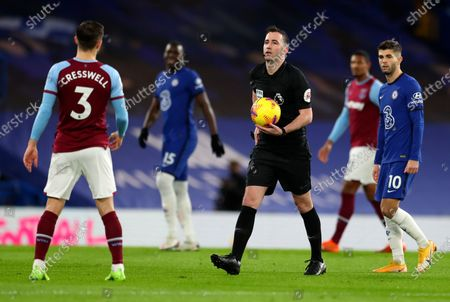 Referee Chris Kavanagh holds the ball prior to the start during the English Premier League soccer match between Chelsea and West Ham at Stamford Bridge, London