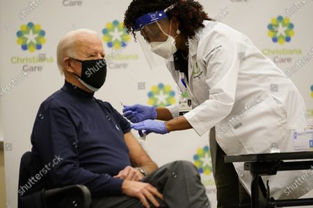 President-elect Joe Biden receives his first dose of the coronavirus vaccine at ChristianaCare Christiana Hospital in Newark, Del., from nurse practitioner Tabe Mase