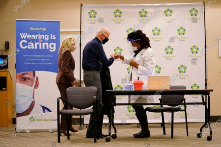 President-elect Joe Biden fist bumps with nurse practitioner Tabe Mase after receiving his first dose of the coronavirus vaccine at ChristianaCare Christiana Hospital in Newark, Del., as Jill Biden looks on