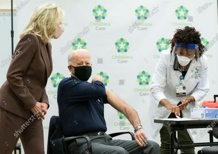 President-elect Joe Biden, joined by his wife Jill Biden, rolls up his sleeve to receive his first dose of the coronavirus vaccine from Nurse partitioner Tabe Mase at Christiana Hospital on live television in Newark Del