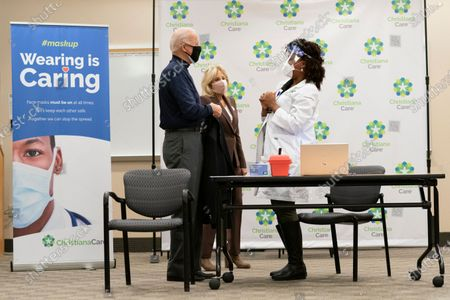 President-elect Joe Biden and his wife Jill Biden talks with nurse partitioner Tabe Mase at Christiana Hospital on live television in Newark Del., after the president-elect receives his first dose of the coronavirus vaccine