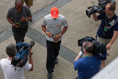 Being backed up by his father Anthony, Lewis Hamilton returns from a press conference after his statement regarding the disqualification at Melbourne.