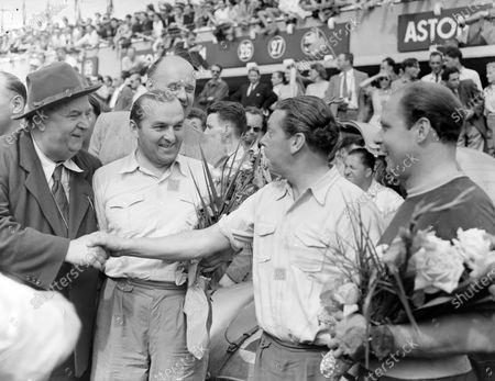 Mercedes racing team manager Alfred Neubauer, shakes hands with the winners Hermann Lang, Fritz Riess and their chief mechanic, carrying their bouquets of flowers.