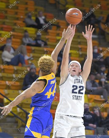 Stock Image of Utah State guard Brock Miller (22) shoots as San Jose State guard Trey Smith (44) defends during the second half of an NCAA college basketball game, in Logan, Utah