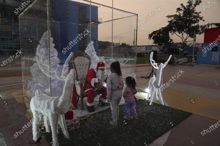 Dressed as Santa Claus, David Pizarro, talks to a couple of girls, from inside a plastic enclosure in an effort to curb the spread of COVID-19, at a square in the Comas municipality of Lima, Peru