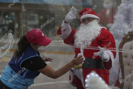 Stock Image of Dressed as Santa Claus, David Pizarro waves from inside a plastic enclosure as a woman disinfects it in an effort to curb the spread of COVID-19, at a square in the Comas municipality of Lima, Peru