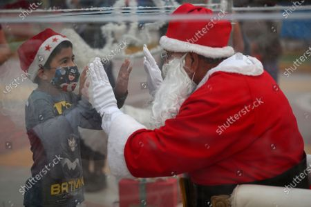 Dressed as Santa Claus, David Pizarro, talks to a boy from inside a plastic enclosure in an effort to curb the spread of COVID-19, at a square in the Comas municipality of Lima, Peru
