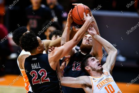 Tennessee's John Fulkerson (10) fights for the rebound with St. Joseph's Jordan Hall (22) and Anthony Longpré (12) during an NCAA college basketball game in Knoxville, Tenn
