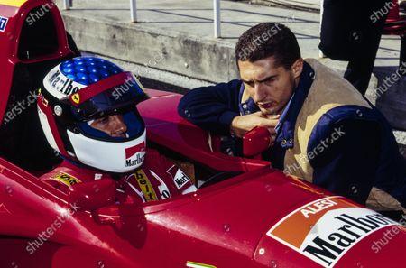 Jean Alesi sits in his Ferrari 412T2 as Italian footballer Daniele Massaro looks on.
