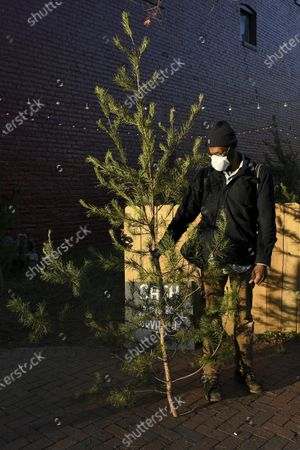 Stock Image of Brian Palmer, of Richmond, holds his recently purchased tree outside of Frank Pichel's tree lot, in Richmond, Va. A Virginia man has found a way to use Charlie Brown-style Christmas trees to benefit a middle school that provides scholarships for students from an impoverished area