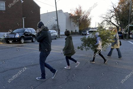 From left, Peter Taffs, Marcie Taffs, 14, Juno Taffs, 11, and Clare Van Loenen walk across the street after buying a tree from Frank Pichel's tree lot, in Richmond, Va. A Virginia man has found a way to use Charlie Brown-style Christmas trees to benefit a middle school that provides scholarships for students from an impoverished area