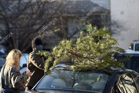 Parker Vivier and Marsden Olsen, both of Richmond, prepare to tie their tree to their car after purchasing from Frank Pichel's tree lot, in Richmond