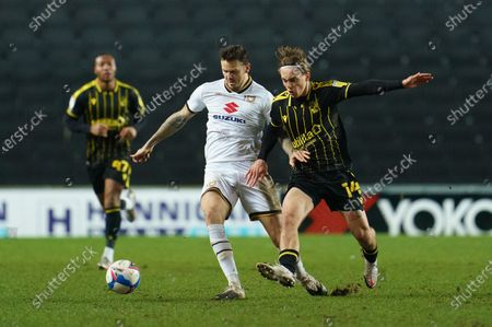 Luke McCormick of Bristol Rovers (14) and Ben Gladwin of MK Dons (7)