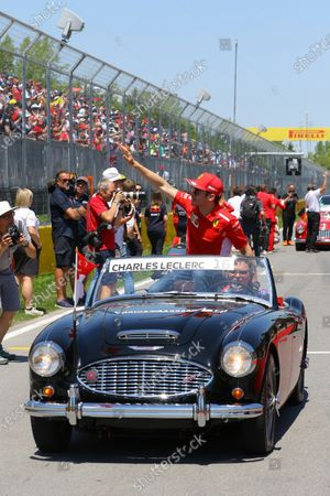 Charles Leclerc, Ferrari, waves from an Austin-Healey on the drivers' parade