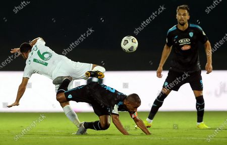 Al-Ahli's player Nouh Al-Mousa (L) in action against Al-Fateh's Mohammed Al-Fuhaid (down) as Al-Fateh's Mitchell Te Vrede (R) looks on during the Saudi Professional League soccer match between Al-Ahli and Al-Fateh at King Abdullah Sport City Stadium, 30 kilometers north of Jeddah, Saudi Arabia, 22 December 2020.