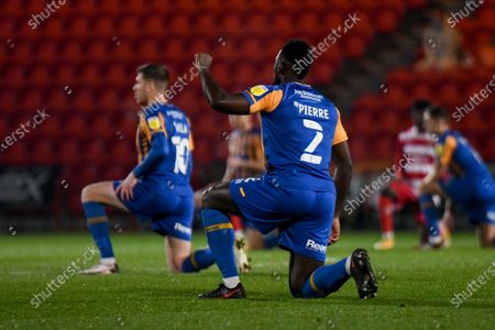 Shrewsbury Town defender Aaron Pierre (2) raises a fist whilst taking a knee during the EFL Sky Bet League 1 match between Doncaster Rovers and Shrewsbury Town at the Keepmoat Stadium, Doncaster