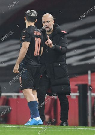 Manchester City's manager Pep Guardiola (R) speaks to Sergio Aguero (L)  during the Carabao Cup quarter final match between Arsenal FC and Manchester City in London, Britain, 22 December 2020.