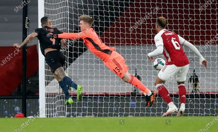Manchester City's Gabriel Jesus, left, heads the ball past Arsenal's goalkeeper Runar Alex Runarsson to score his team's first goal during the English League Cup quarterfinal soccer match between Arsenal and Manchester City at Emirates Stadium, London