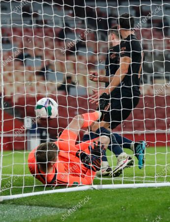 Arsenal's goalkeeper Runar Alex Runarsson falls to the ground after failing to stop Manchester City's Aymeric Laporte scoring his team's fourth goal during the English League Cup quarterfinal soccer match between Arsenal and Manchester City at Emirates Stadium, London
