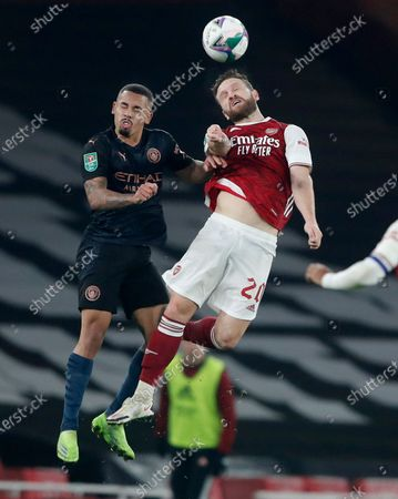 Manchester City's Gabriel Jesus, left, and Arsenal's Shkodran Mustafi compete to head the ball during the English League Cup quarterfinal soccer match between Arsenal and Manchester City at Emirates Stadium, London